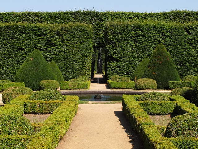 large garden with green hedges and a fountain